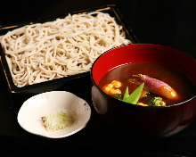 Chilled buckwheat soba noodles on a bamboo strainer with vegetables served