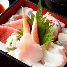 Seafood served over rice in a lacquered box