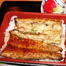 Large eel served over rice in a lacquered box