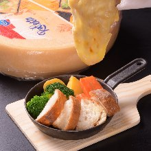 Cooked vegetables and baguette topped with raclette