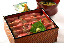 Roast beef served over rice in a lacquered box